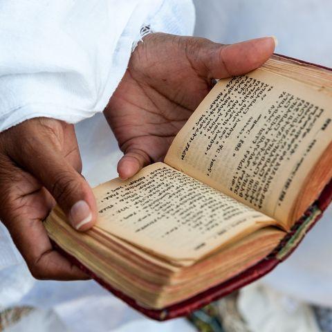 Katholischer Priester mit einem Gebetsbuch auf Amharisch, Äthiopien