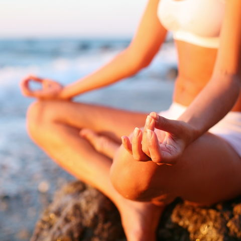 Meditierende Frau an der Küste, Ayurveda