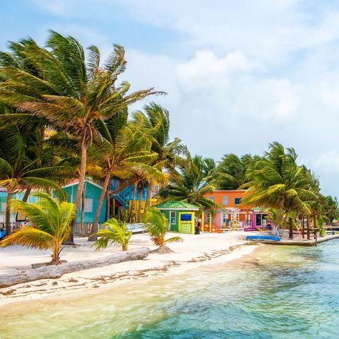 Farbtupfer in Form von Häuslein am Strand von Caye Caulker, Belize