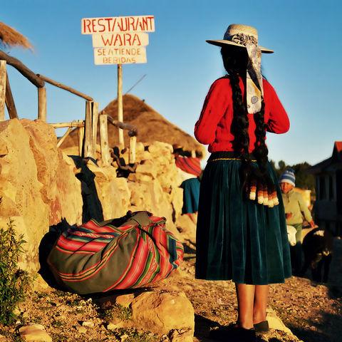 Bolivianische Frau mit Sack und Pack auf der Sonneninsel (Isla del Sol) im Herzen des Titicacasees, Bolivien