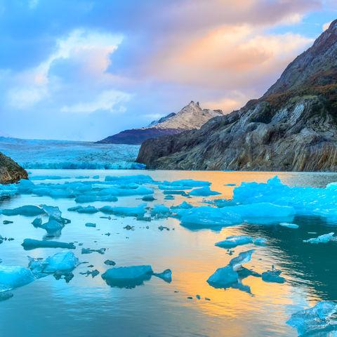 Bei Sonnenaufgang leuchtende Eisschollen des Grey Gletschers im Torres del Paine Nationalpark, Chile