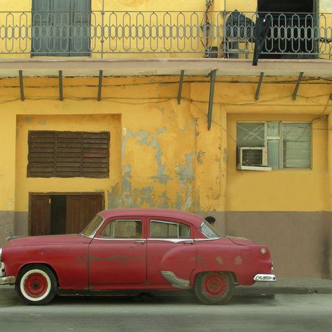 Roter Oldtimer vor gelber Wand, Kuba