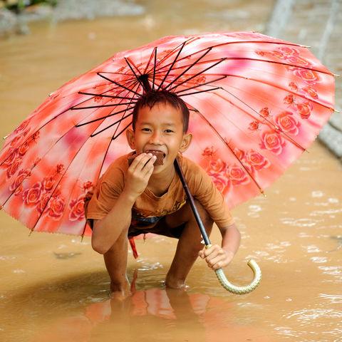 Spielendes Kind im Regen, Indonesien