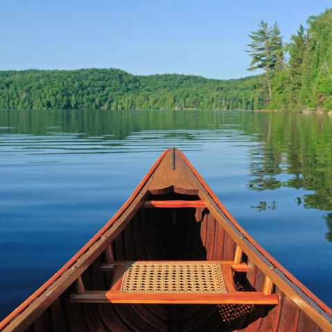 Kanufahrt durch einen stillen klaren Bergsee, Kanada