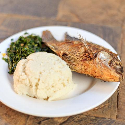 Kenias Nationalgericht Ugali (Getreidebrei) mit Fisch und Gemüse, Kenia