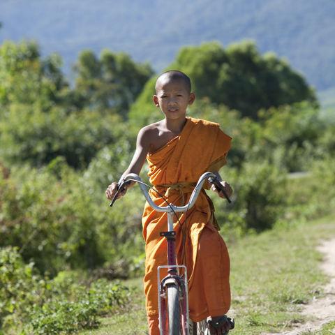 Junger Mönch auf einem Fahrrad, Laos