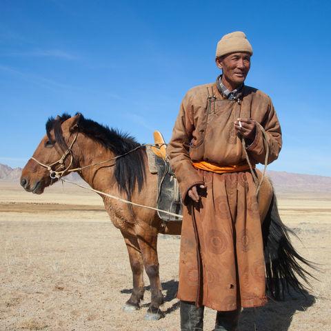 Ein Nomade mit seinem Pferd in der Steppe, Mongolei