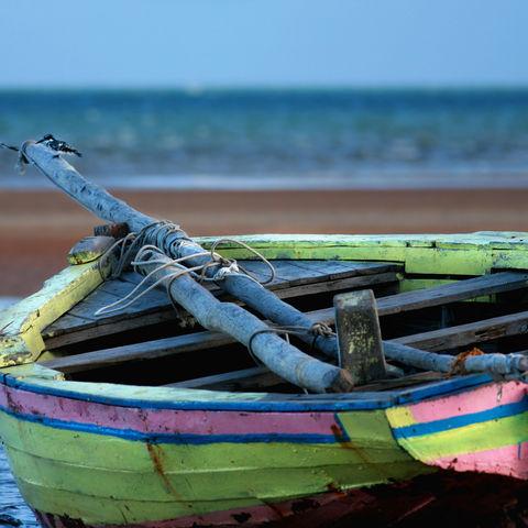 Buntes Boot bei Ebbe an der Küste, Mosambik