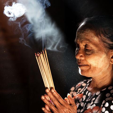 Frau betet mit Räucherstäbchen, Myanmar