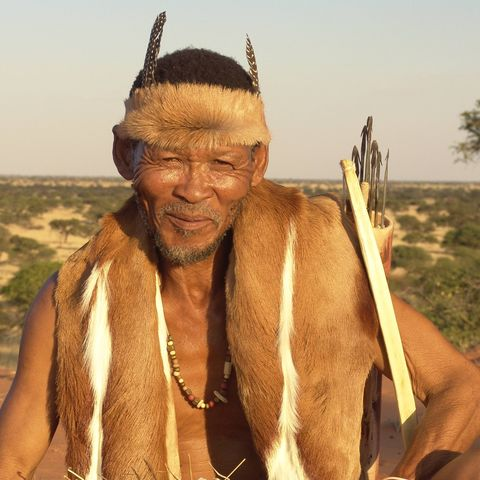 San in traditioneller Kleidung in der Kalahari-Savanne, Namibia