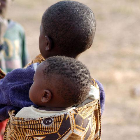 Mädchen tragt ihr Geschwisterchen auf dem Rücken, Sambia