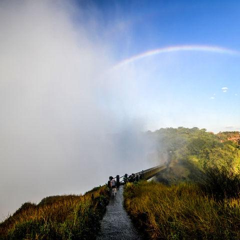 Regenbogen über der aufspritzenden Gischt der Viktoriafälle, Sambia