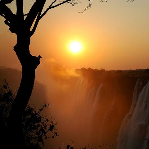 Die Sonne taucht mit ihren letzten Strahlen die Viktoriafälle in magisches Licht, Simbabwe