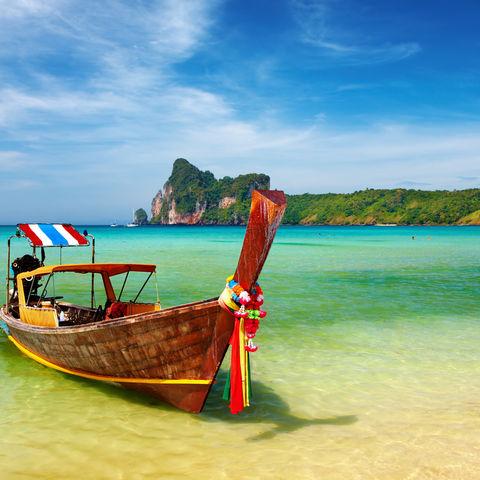 Boot im kristallklaren Wasser, Thailand