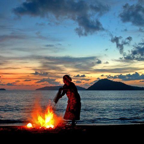 Lagerfeuer am Strand mit einem Ausblick auf die vorgelagerten Inseln, Thailand