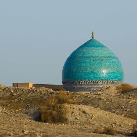 Türkise Kuppel einer Mosche vor dem Wüstensand in Buchara, Usbekistan